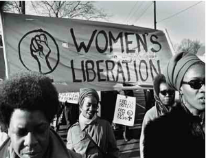 "Black feminists holding up a banner that reads ""WOMEN"